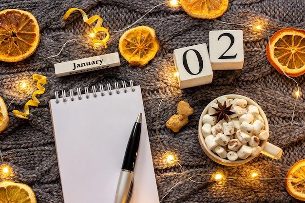 Kalendarz 2 stycznia puchar kakao i pusty notatnik otwarty