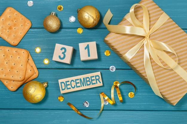 Kalendarz 31 grudnia z pudełkiem prezentów, krakersami i ozdóbkami świątecznymi