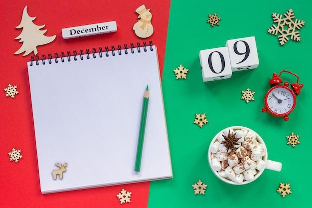 Kalendarz 9 grudnia szklanka kakao i pianki, pusty otwarty notatnik