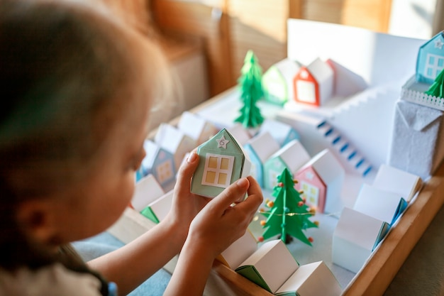 Kalendarz adwentowy origami. śliczna dziewczyna patrząc na małe papierowe domki, sezonowa aktywność z dziećmi