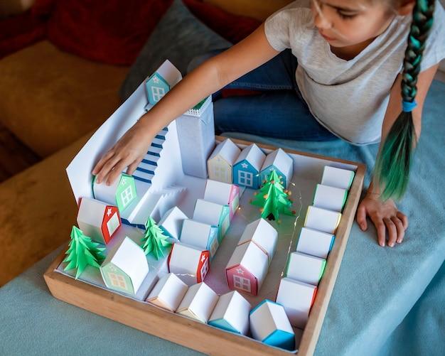 Kalendarz adwentowy origami. śliczna dziewczyna patrząc na małe papierowe domy z numerem