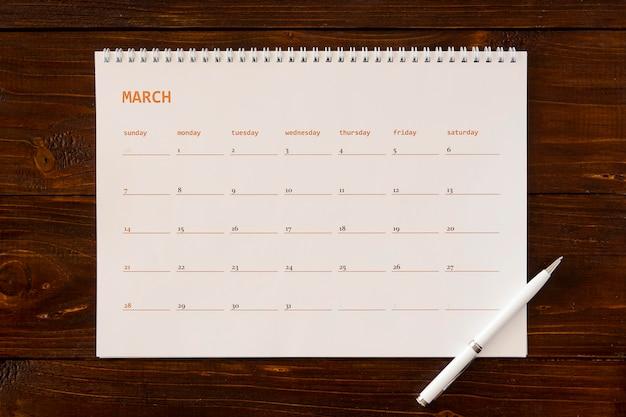 Kalendarz biurkowy leżący na płasko na drewnianym stole