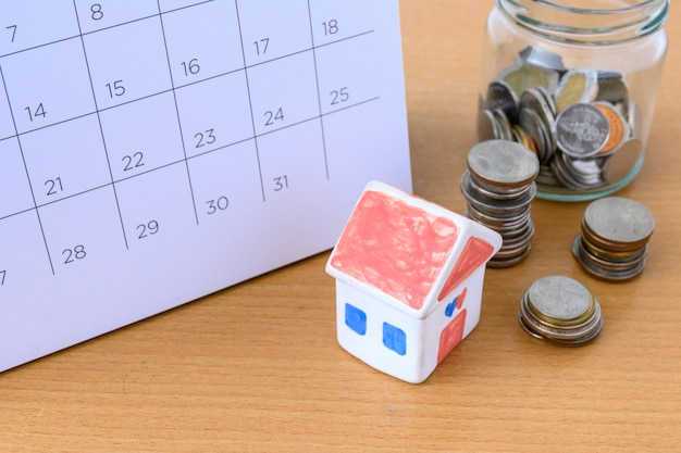 Kalendarz i dom na stole. dzień zakupu lub sprzedaży domu lub płatności za czynsz lub pożyczkę.