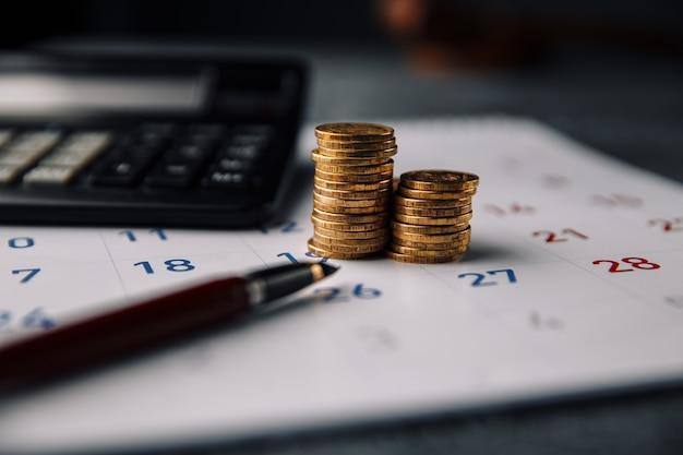 Kalendarz, kalkulator i stos monet w biurze.