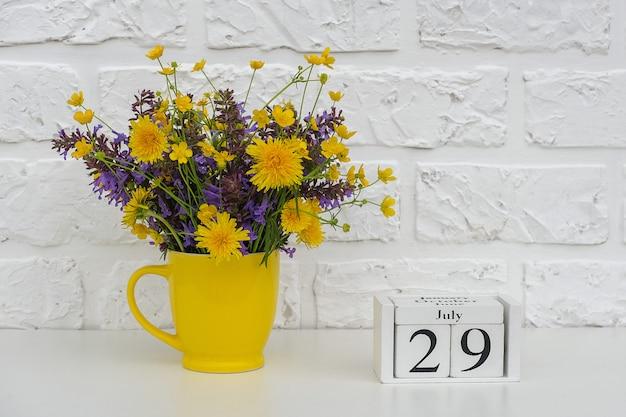 Kalendarz kostek 29 lipca i żółty kubek z jasnymi kolorowymi kwiatami