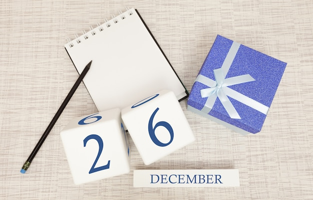 Kalendarz kostki na 26 grudnia i pudełko upominkowe, w pobliżu notesu z ołówkiem