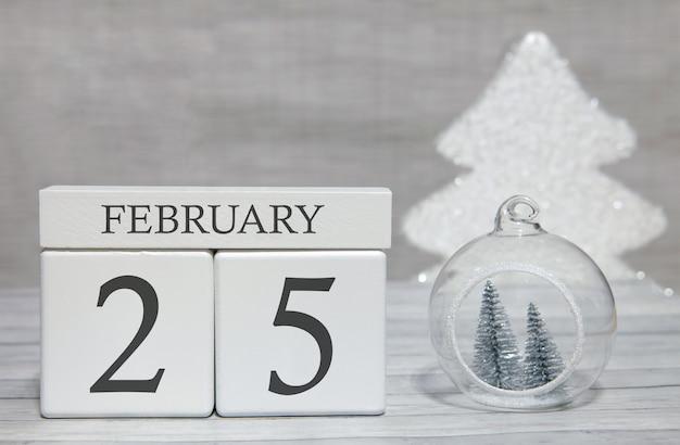 Kalendarz kształtu kostki na 25 lutego na powierzchni drewnianych i jasnym tle