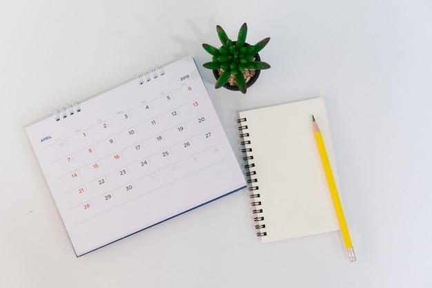 Kalendarz kwietnia 2019 z notebooka, długopis i roślin na biurku z koncepcją widok z góry