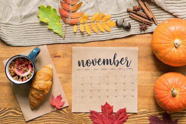 Kalendarz listopadowy z gorącym napojem i rogalikiem, w pobliżu dojrzałe dynie, jesienne liście i przyprawy