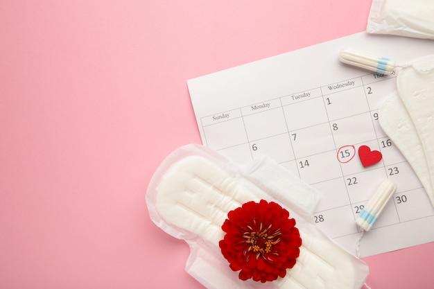 Kalendarz menstruacyjny z bawełnianymi tamponami i podpaskami na różowym tle. kobiety krytyczne dni, ochrona higieny kobiety. bóle menstruacyjne