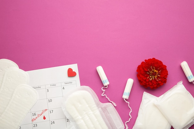 Kalendarz menstruacyjny z bawełnianymi tamponami i podpaskami z kwiatkiem na różowym tle. kobiety krytyczne dni, ochrona higieny kobiety. bóle menstruacyjne. widok z góry