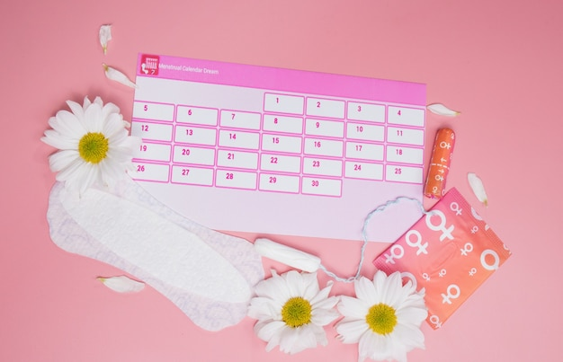 Kalendarz menstruacyjny z bawełnianymi tamponami, podpaskami, białym kwiatkiem