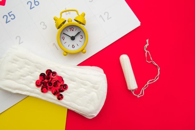 Kalendarz menstruacyjny z kobiecymi produktami i żółtym budzikiem na kolorowym
