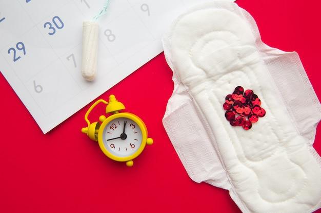 Kalendarz miesiączkowy z podpaską i żółtym budzikiem na czerwono.