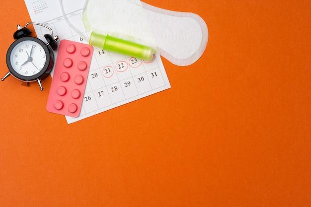 Kalendarz miesiączkowy z podpaskami i tamponami, pigułki