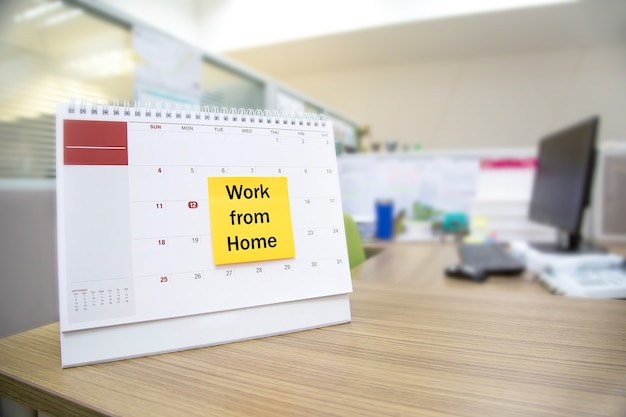 Kalendarz na biurku z papierową notatką pracy z domu.