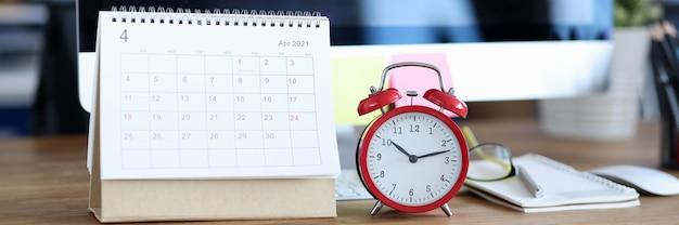 Kalendarz na kwiecień jest na pulpicie obok budzika planowania rozwoju biznesu na miesiąc