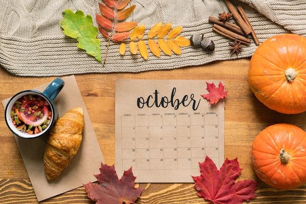 Kalendarz październikowy wśród świeżego ciasta z herbatą, dojrzałymi dyniami, liśćmi i przyprawami na drewnianym stole
