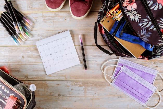 Kalendarz, plecak i maska na stole.