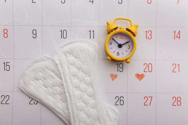 Kalendarz, podpaski menstruacyjne i żółty budzik.