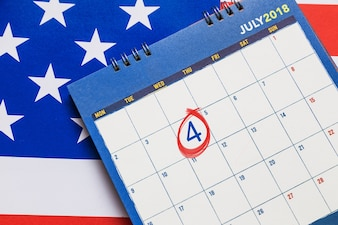 Kalendarz przedstawiający miesiąc lipiec z czerwonym kółkiem na 4 dzień z amerykańską flagą w tle