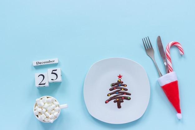 Kalendarz świąteczny 25 grudnia. słodka czekoladowa choinka na talerzu, sztućce w czapce mikołaja