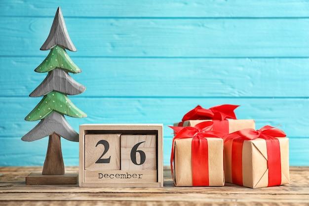 Kalendarz z datą i pudełkami prezentowymi na kolorowym tle. koncepcja bożego narodzenia