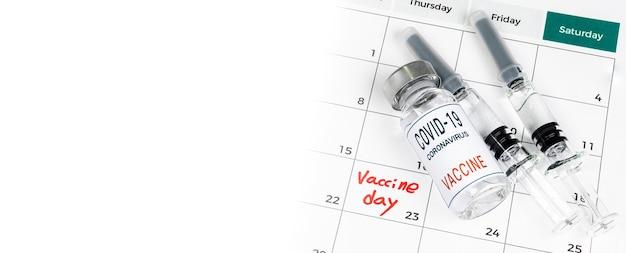 Kalendarz z datami szczepień, szczepionką covid-19 i koncepcją medyczną ze strzykawką.