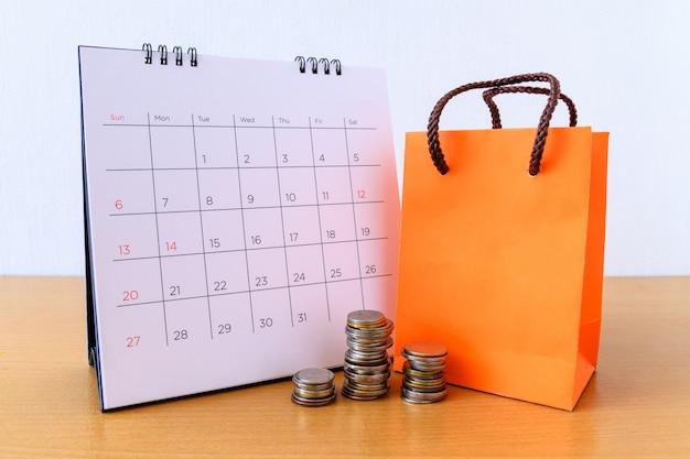 Kalendarz z dniami i pomarańczowa papierowa torba na drewnianym stole. koncepcja zakupów