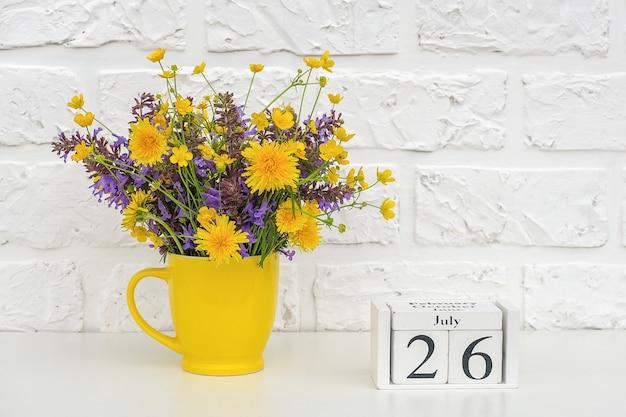 Kalendarz z drewnianymi kostkami 26 lipca i żółty kubek z jasnymi kwiatami na tle białej cegły