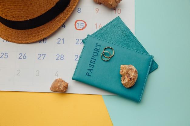 Kalendarz z paszportami, kapeluszem i pierścieniami na kolorowej powierzchni. miesiąc miodowy, koncepcja ślubu