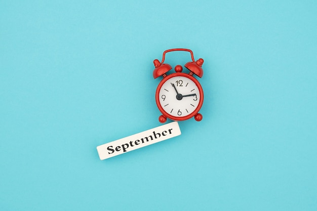 Kalendarzowy miesiąc jesieni września i czerwony budzik na niebieskim papierze