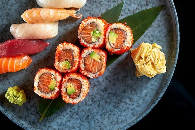 Kalifornijska rolka sushi z łososiem w kawiorze tobiko i różnymi sushi. sushi z łososiem, tuńczykiem, krewetkami