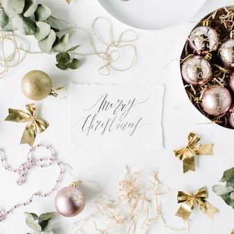 Kaligrafia słowa wesołych świąt i ramka wykonana ze świątecznych dekoracji z bombkami, świecidełkiem, kokardką, eukaliptusem. boże narodzenie