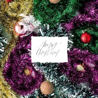 Kaligrafia słowa wesołych świąt i świątecznych dekoracji z kolorowymi szklanymi kulkami, świecidełkami, zabawkami. leżał płasko, widok z góry