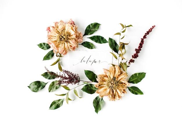 Kaligrafia słowo jesień i okrągły wzór wieniec ramki, beżowe suszone piwonie kwiaty, gałęzie i liście na białym tle