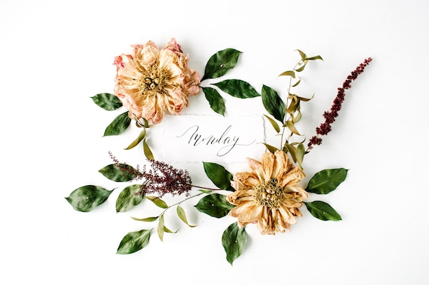 Kaligrafia słowo poniedziałek i okrągły wzór wieniec ramki, beżowe suszone piwonie kwiaty, gałęzie i liście na białym tle