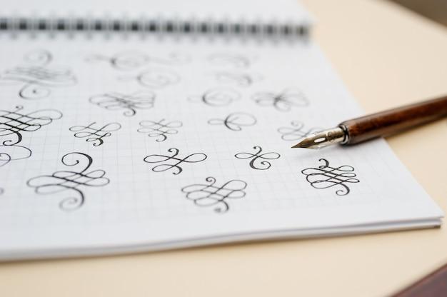 Kaligraficzny rozkwita w albumie i długopisie na stole
