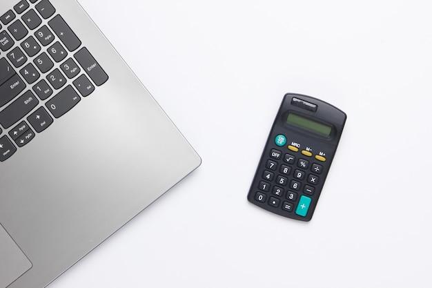 Kalkulacja ekonomiczna, analiza zysków. kalkulator i laptop na białym.