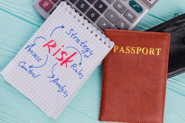 Kalkulacja kosztów urlopu. paszport zeszyt kalkulatora na drewnianej podłodze. widok z góry.