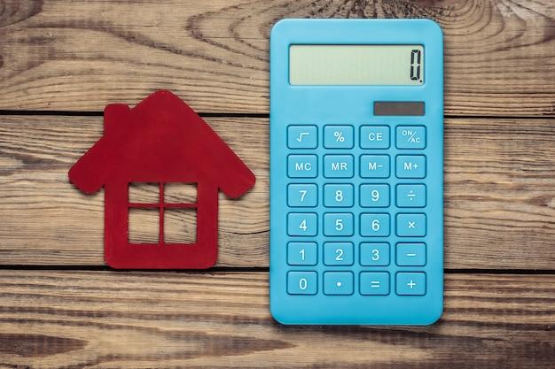 Kalkulacja kosztów wynajmu lub zakupu domu. kalkulator z czerwoną postacią domu na drewnianym