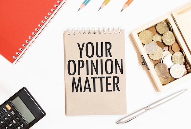 Kalkulator, czerwony notes, trzy kolorowe kredki, srebrny długopis i brązowy notatnik z tekstem twoja opinia ma znaczenie