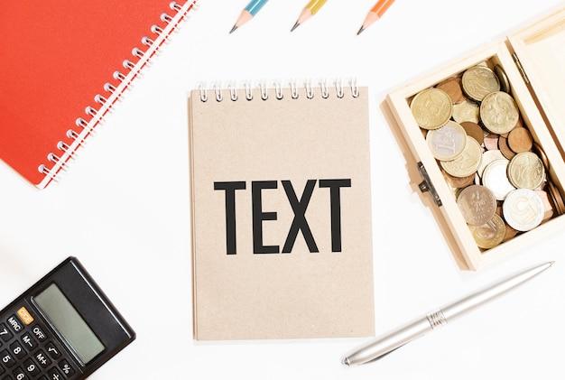 Kalkulator, czerwony notes, trzy kolorowe kredki, srebrny długopis i brązowy notes z tekstem text