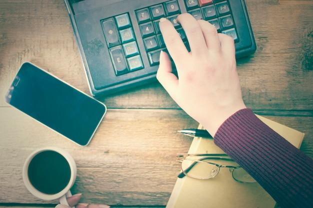 Kalkulator dłoni kobiety i kawa na stole roboczym