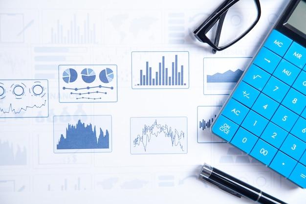 Kalkulator, długopis, okulary na wykresach finansowych