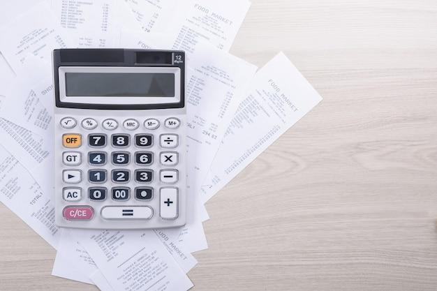 Kalkulator do liczenia na stosie czeków z zakupów w sklepie na drewnianym tle