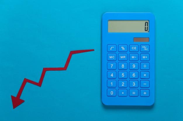 Kalkulator i czerwona strzałka spadek. wykres upadku spada. recesja gospodarcza, kryzys