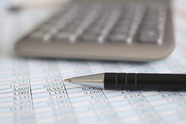 Kalkulator i długopis leżący na dokumencie z zbliżeniem liczb