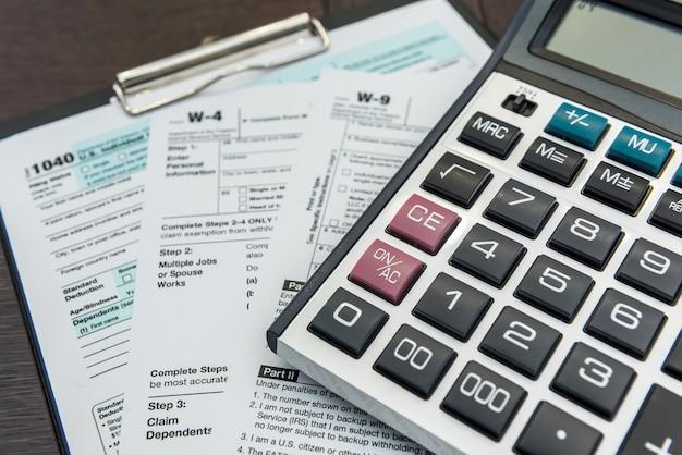 Kalkulator i długopis leżący na formularzu federalnym