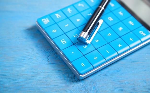 Kalkulator i długopis na niebieskim tle